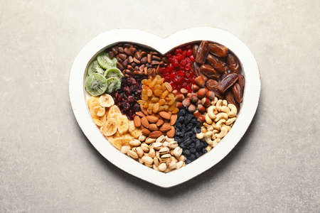 Heart shaped plate with different dried fruits and nuts on table