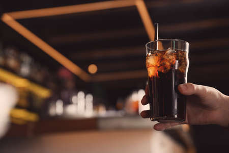 Man holding glass of refreshing cola indoors, closeup. Space for text Banque d'images