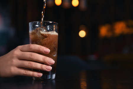 Woman holding glass with ice cubes while pouring cola at table indoors, closeup. Space for text Banque d'images