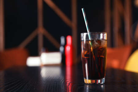 Glass of refreshing cola with ice on table indoors. Space for text