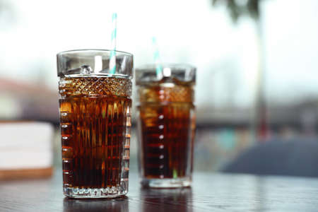 Glasses with refreshing cola and ice cubes on table indoors. Space for text