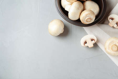 Fresh champignon mushrooms and plate on table, top view. Space for text Standard-Bild - 115880550