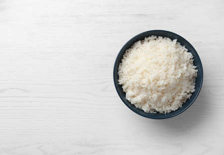 Bowl of boiled rice on wooden background, top view with space for text Imagens