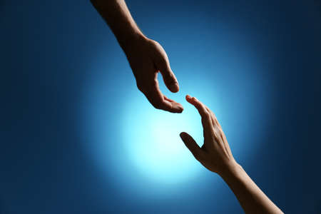 Man reaching for woman's hand on color background, closeup. Help and support concept