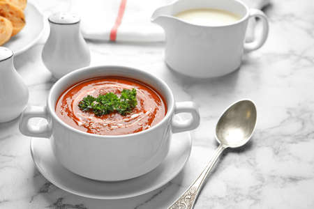 Dish with fresh homemade tomato soup on marble table. Space for text