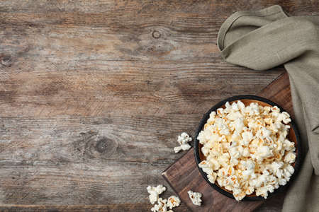 Flat lay composition with popcorn and space for text on wooden background