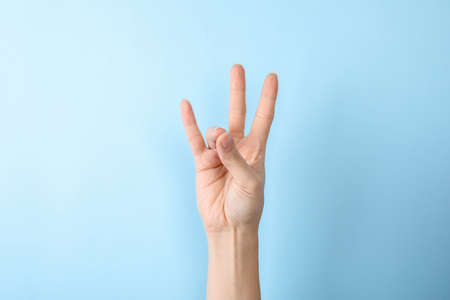 Woman showing number seven on color background, closeup. Sign language Stock Photo