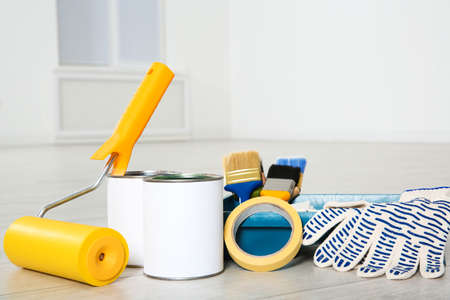 Cans of paint and decorator tools on wooden floor indoors