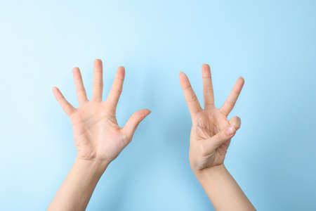 Woman showing sign eight on color background, closeup. Body language Stock Photo
