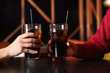 Young couple with glasses of refreshing cola at table indoors, closeup Banque d'images