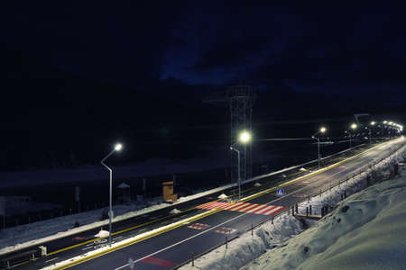 Lit road with snow on sides in evening