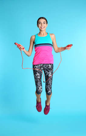 Full length portrait of young sportive woman training with jump rope on color background