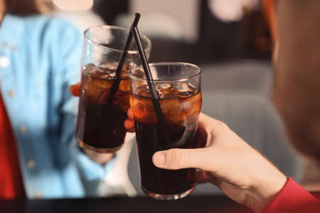 Young couple with glasses of cola at table indoors, closeup