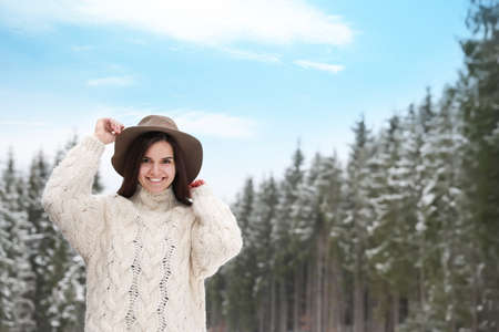 Young woman in warm sweater near snowy forest, space for text. Winter vacation Banque d'images