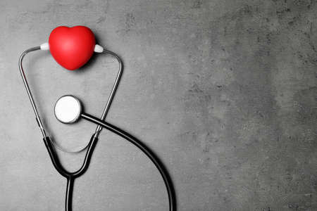 Stethoscope and red heart with space for text on grey background, top view
