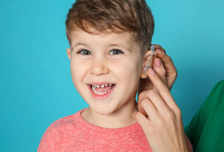 Young woman adjusting little son's hearing aid on color background, closeup 스톡 콘텐츠