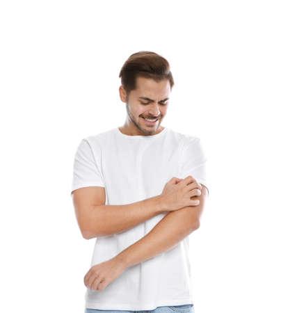 Jonge man krabben arm op witte achtergrond. Vervelende jeuk Stockfoto