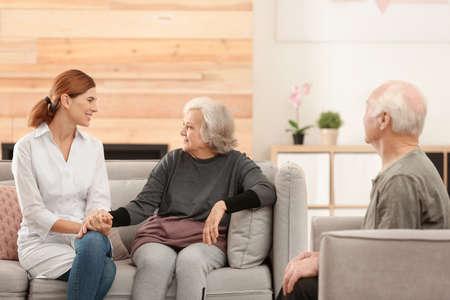 Coniugi anziani con badante femminile in soggiorno