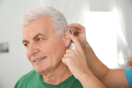 Young man putting hearing aid in fathers ear indoors Stock Photo