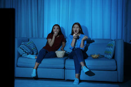 Friends with bowl of popcorn watching TV together on sofa in dark living room