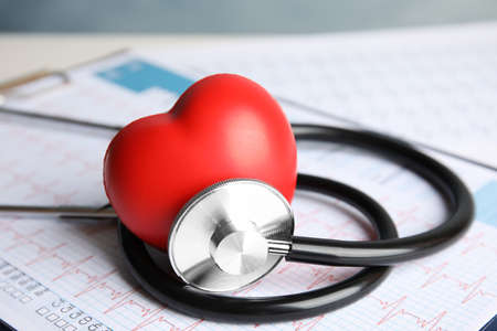 Stethoscope, red heart and cardiogram on table. Cardiology concept Standard-Bild