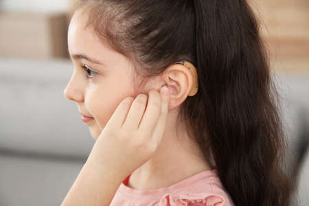 Little girl adjusting hearing aid at home