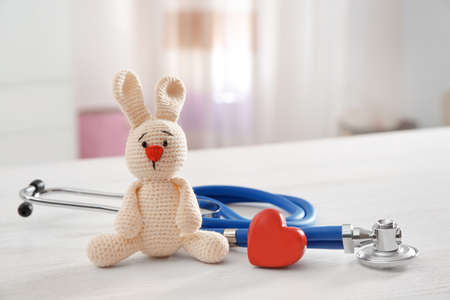 Toy bunny, stethoscope and heart on table indoors, space for text. Childrens doctor