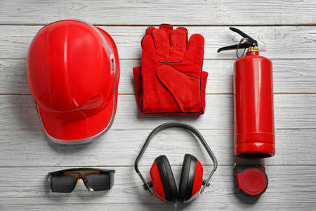 Flat lay composition with safety equipment on wooden background