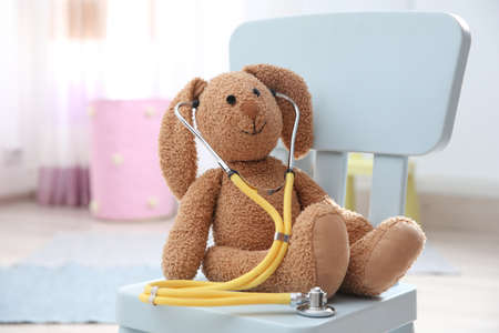 Toy bunny with stethoscope on chair indoors. Childrens doctor Stock Photo