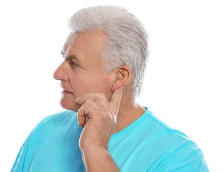 Mature man adjusting hearing aid on white background Stock Photo