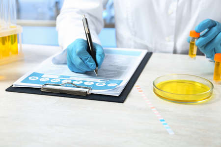 Laboratory assistant with urine sample for analysis writing results of tests at table indoors, closeup Standard-Bild - 115950390