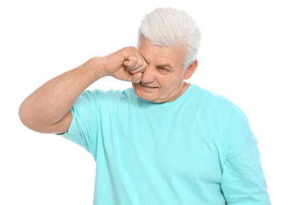 Mature man rubbing eye on white background. Annoying itch Stock Photo