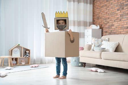 Cute little boy playing cardboard armor in living room Stock fotó