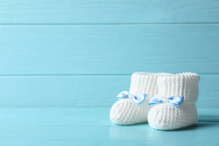 Handmade baby booties on table against wooden background. Space for text Stockfoto