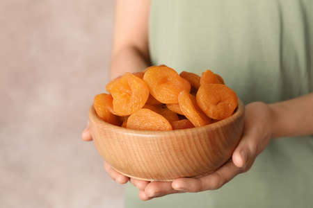 Woman holding bowl with dried apricots on color background, space for text. Healthy fruit