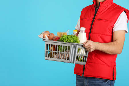 Man holding basket with fresh products on color background, closeup. Food delivery service