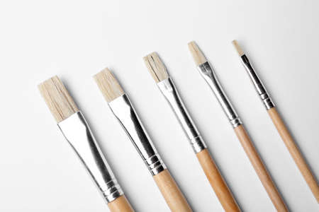 Different paint brushes on white background, top view
