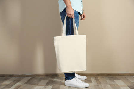 Young man holding textile bag against color wall, closeup. Mockup for design