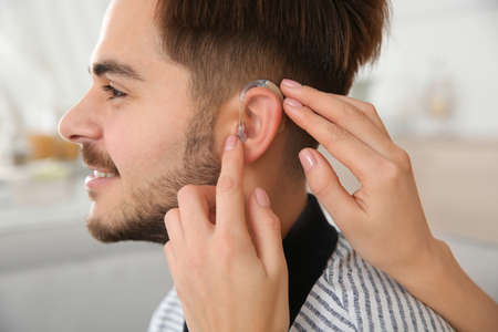 Woman putting hearing aid in mans ear indoors, closeup