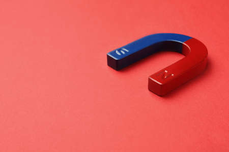 Red and blue horseshoe magnet on color background. Space for text Reklamní fotografie