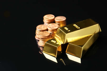 Shiny gold bars and coins on black background Stock Photo