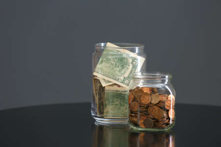 Donation jars with money on table against grey background