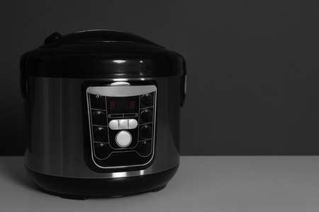 Modern electric multi cooker on table against dark background. Space for text
