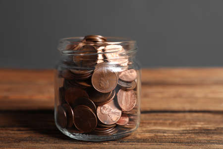 Donation jar with coins on wooden table against grey background Stock Photo