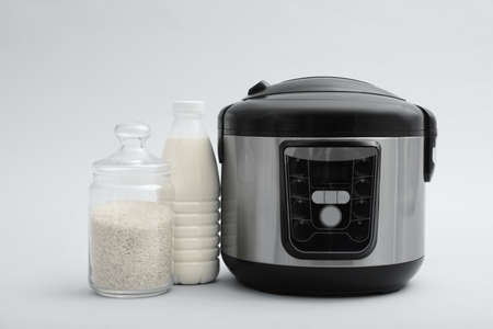 Modern electric multi cooker, rice and milk on grey background Stock Photo