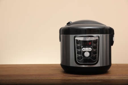 Modern electric multi cooker on table against color background. Space for text