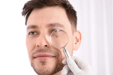 Dermatologist examining patient with magnifying glass in clinic