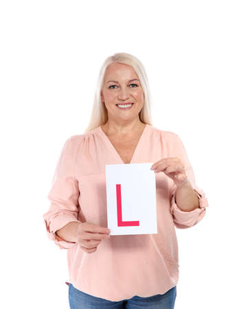 Happy mature woman with L-plate on white background. Getting driving license