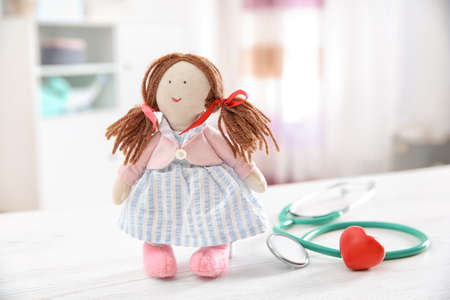Doll, stethoscope and heart on table indoors. Children's doctor