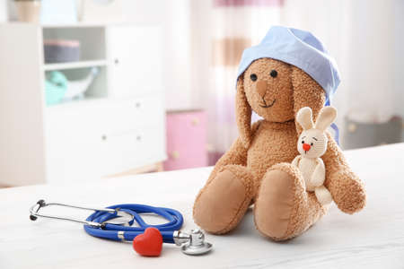 Composition with toy bunnies, stethoscope and heart on table indoors, space for text. Childrens doctor